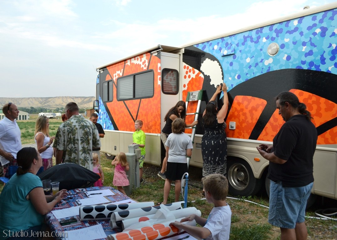 Fulltime Families placing orange vinyl decals on side of butterfly motorhome.