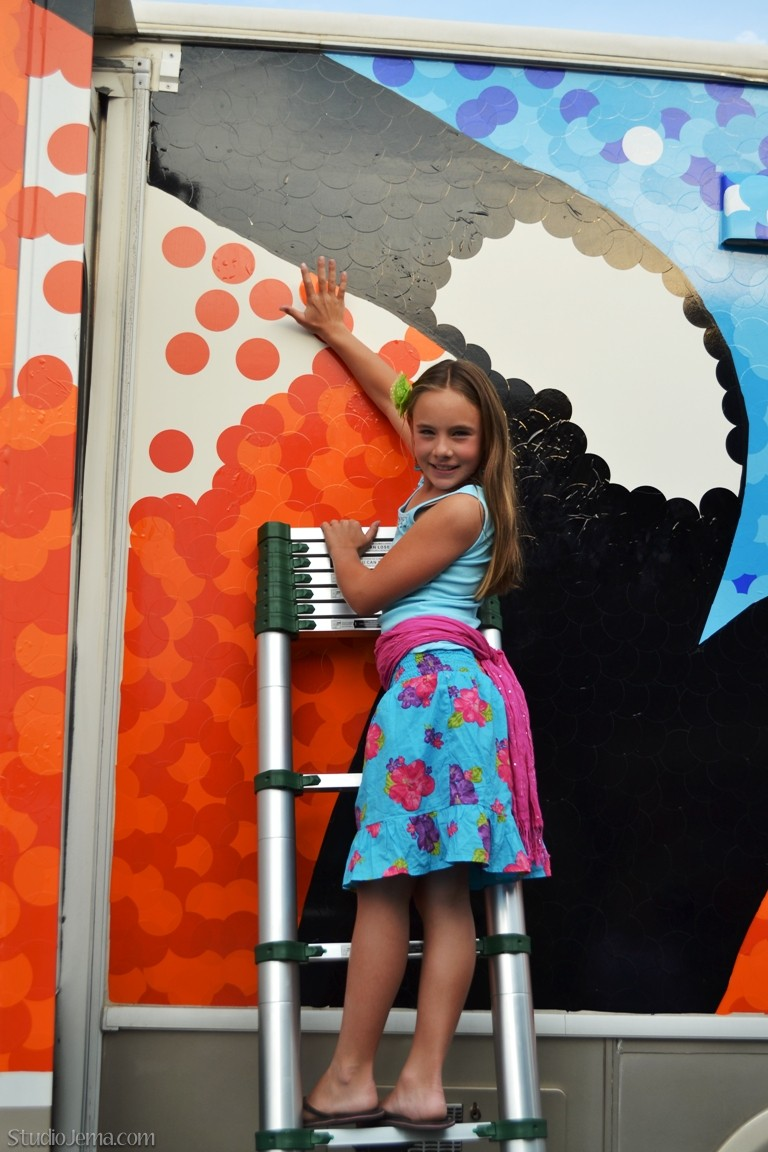 Girl adding orange decal dot to side of inspire to inspire public art project.