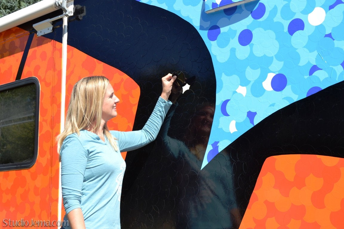 """Jema placing last black vinyl decal dot on her public art project butterfly """"Inspire to Inspire"""""""