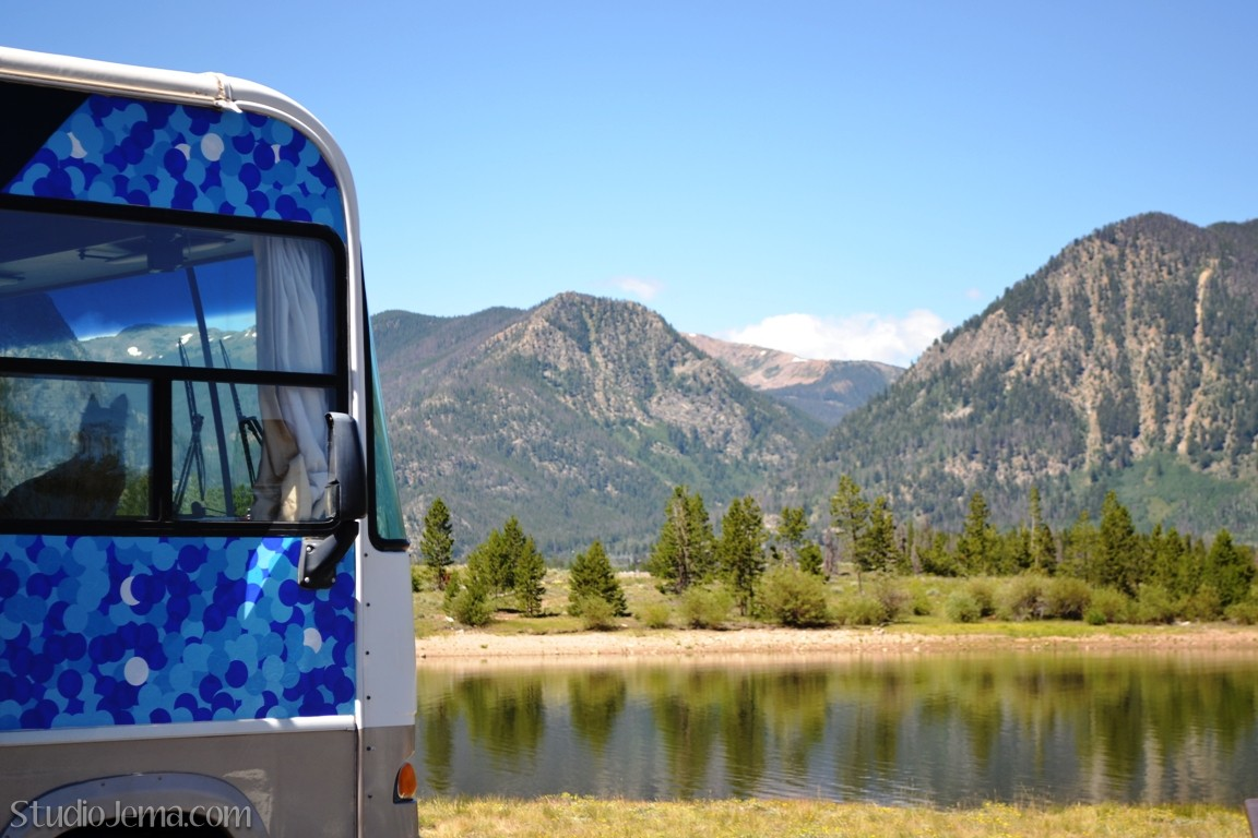 RV parked in front of lake with Colorado Mountains.