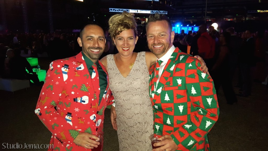 Guys with red Christmas tree party suits.